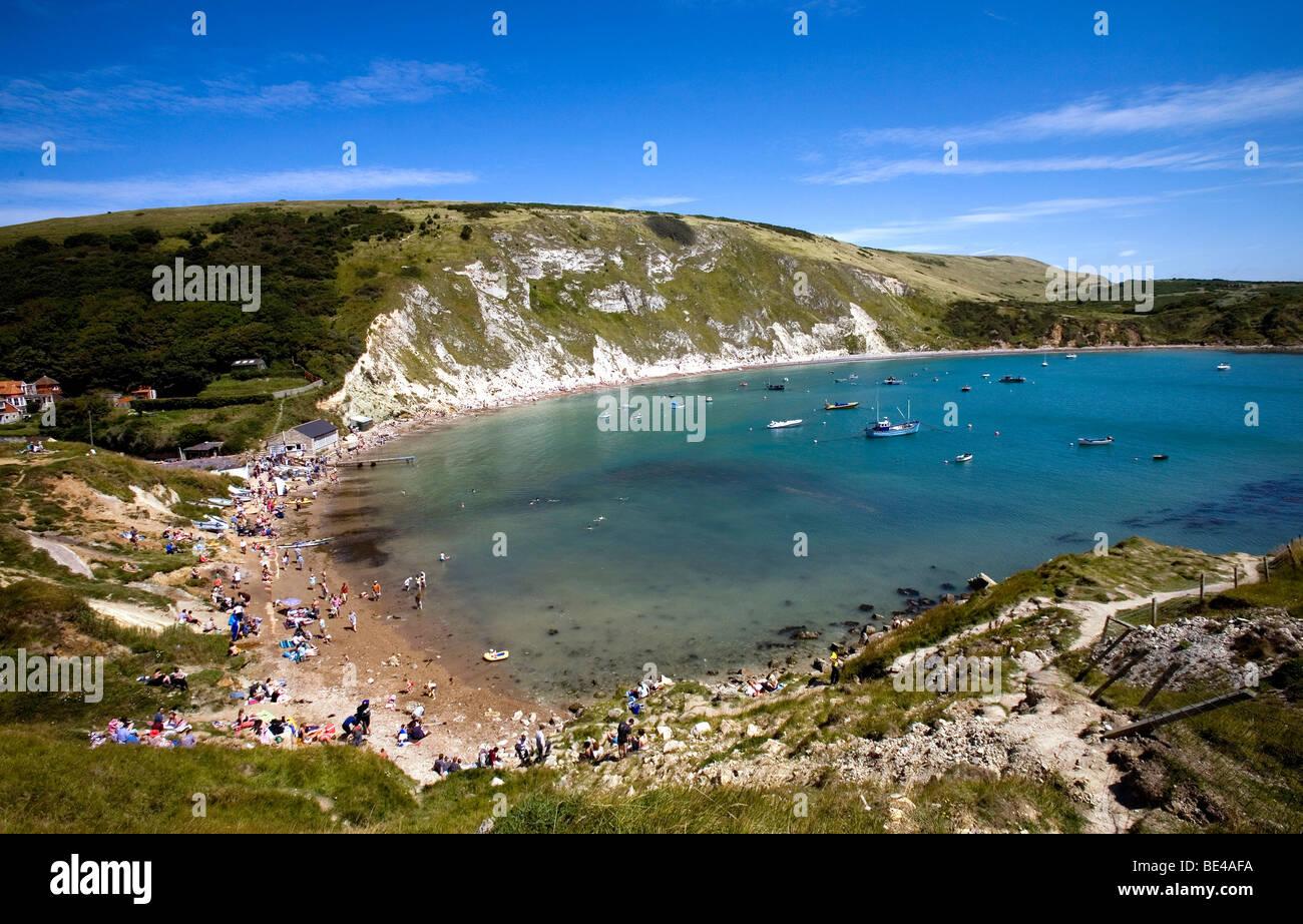 sunbathers tourists enjoying the summer sunshine down on lulworth cove dorset south england Stock Photo