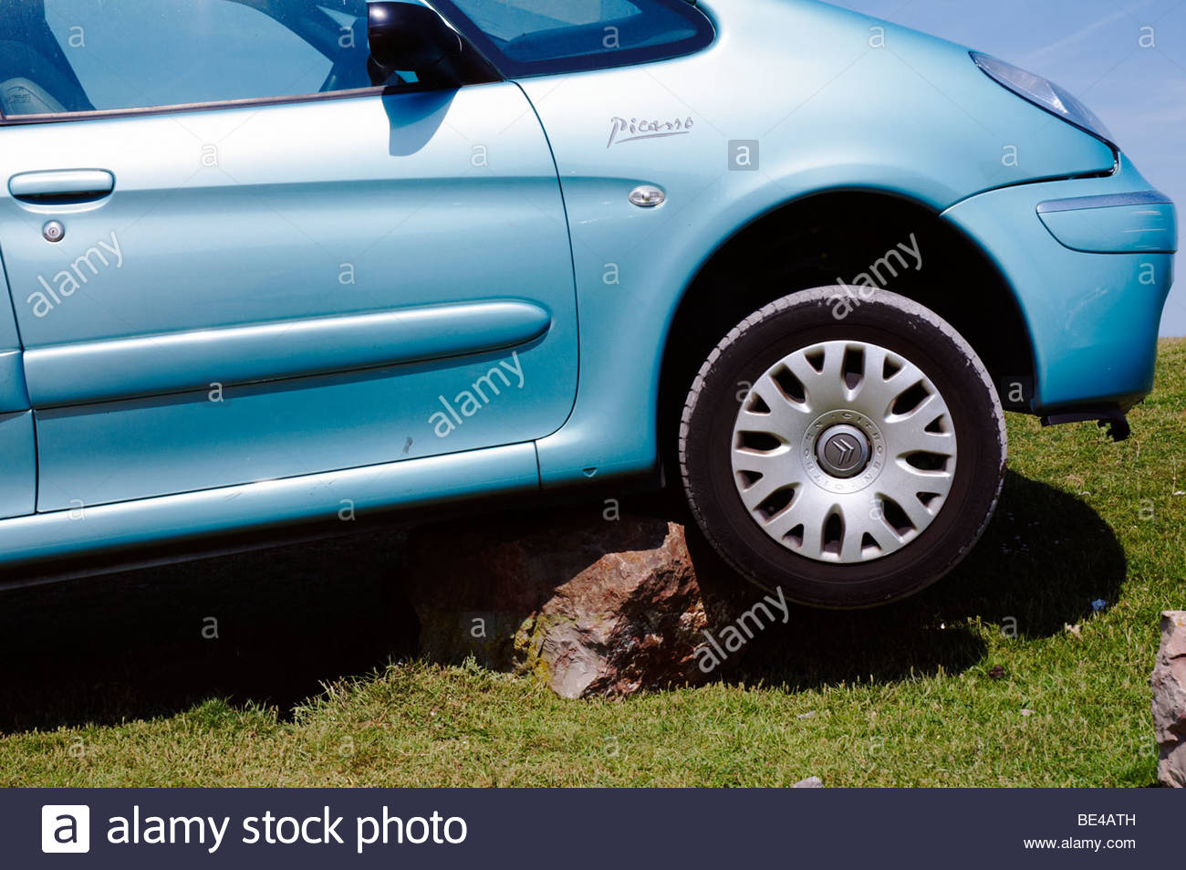 a motor car who's driver didn't apply the handbrake properly when parking and rolled back onto a large boulder - Stock Image