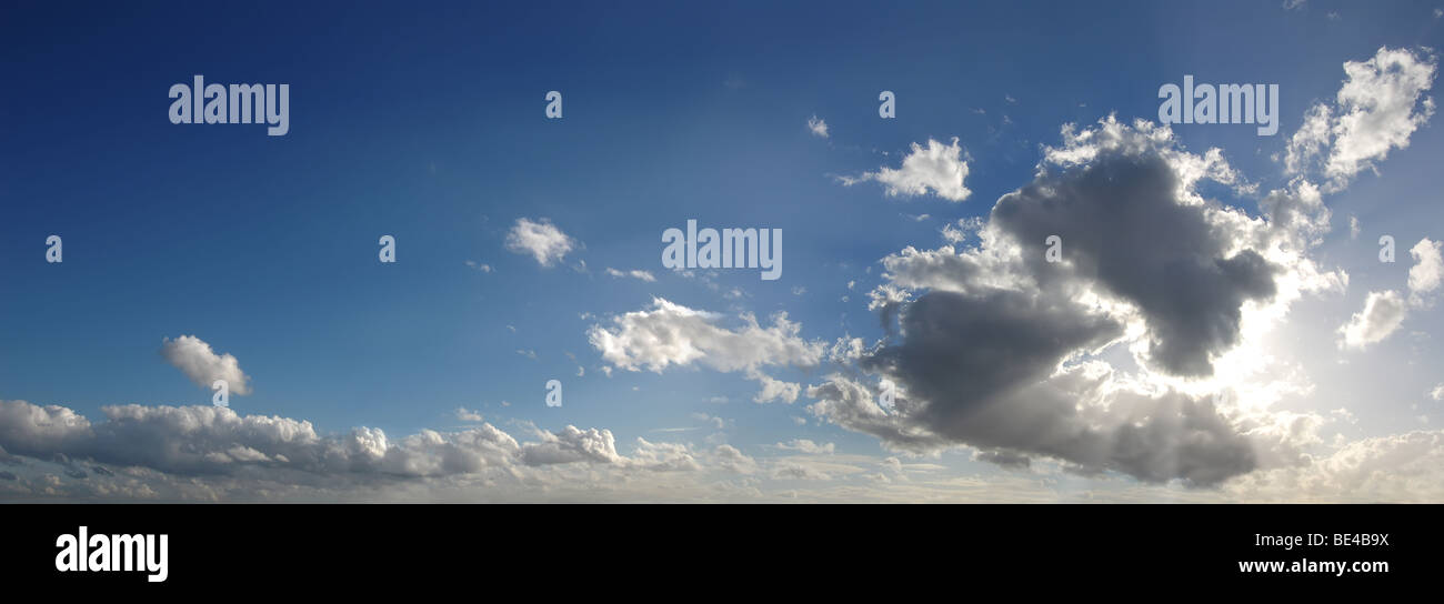Blue sky with clouds obstructing the sun, panoramic dramatic picture - Stock Image