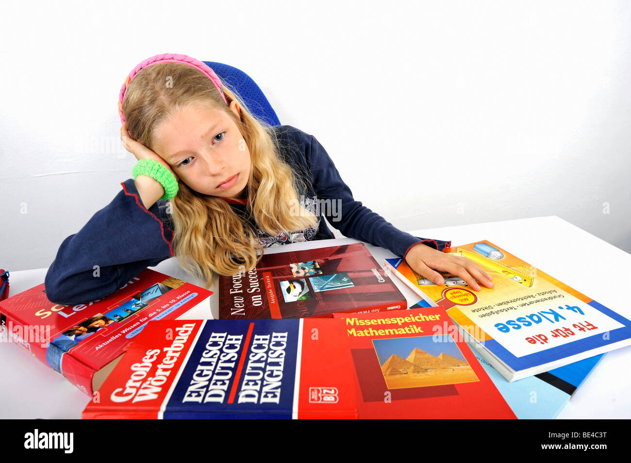 Young schoolgirl is overburdened by her workload, school stress - Stock Image