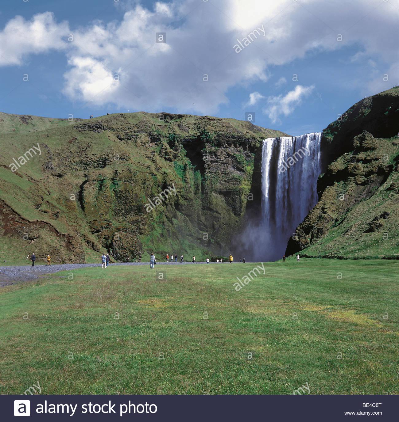 Tourists looking at a waterfall, Skogafoss, Rangarvallasysla, Iceland Stock Photo