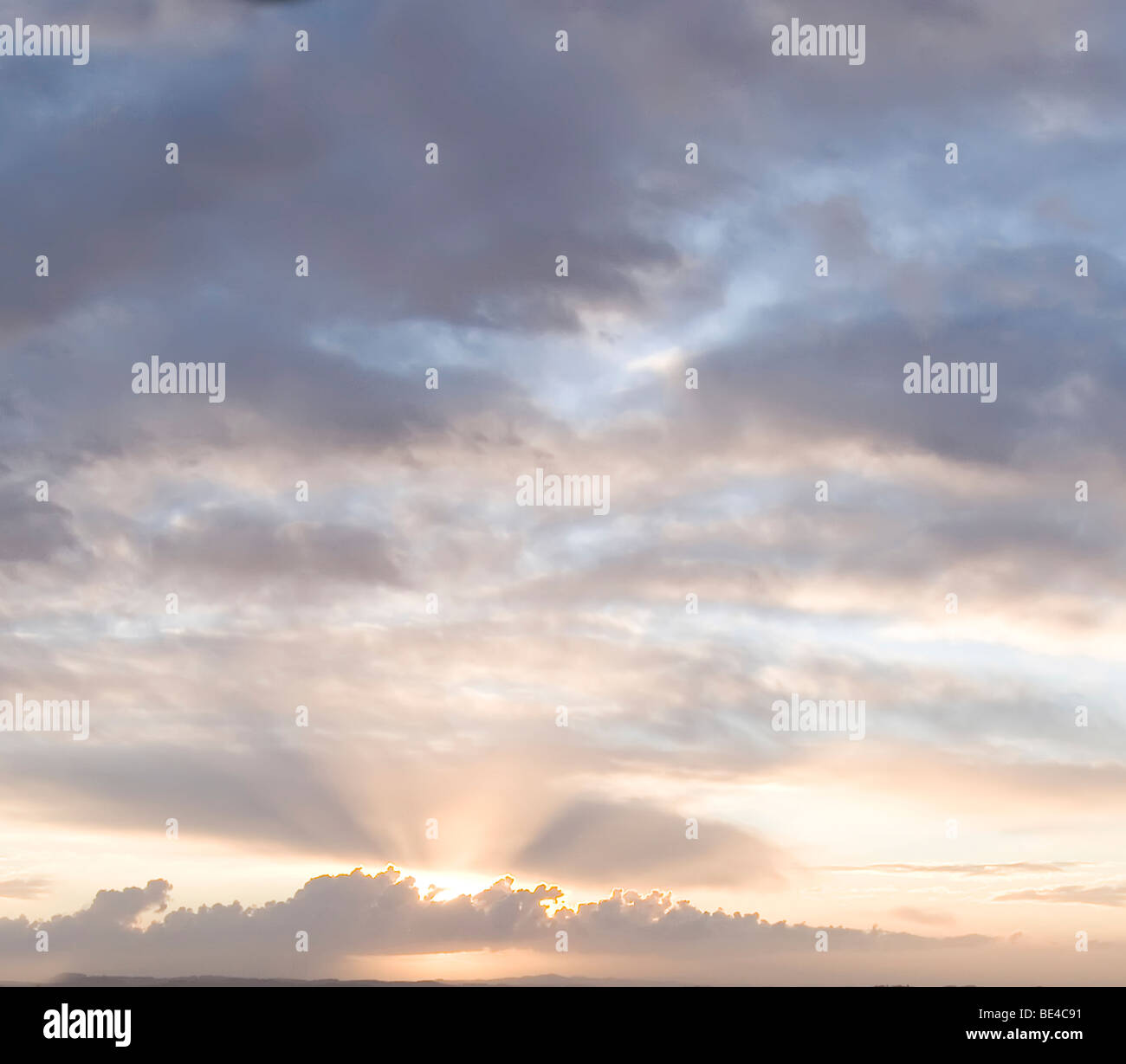 Sunrise/sunset sky with clouds and sun rays/beams - Stock Image
