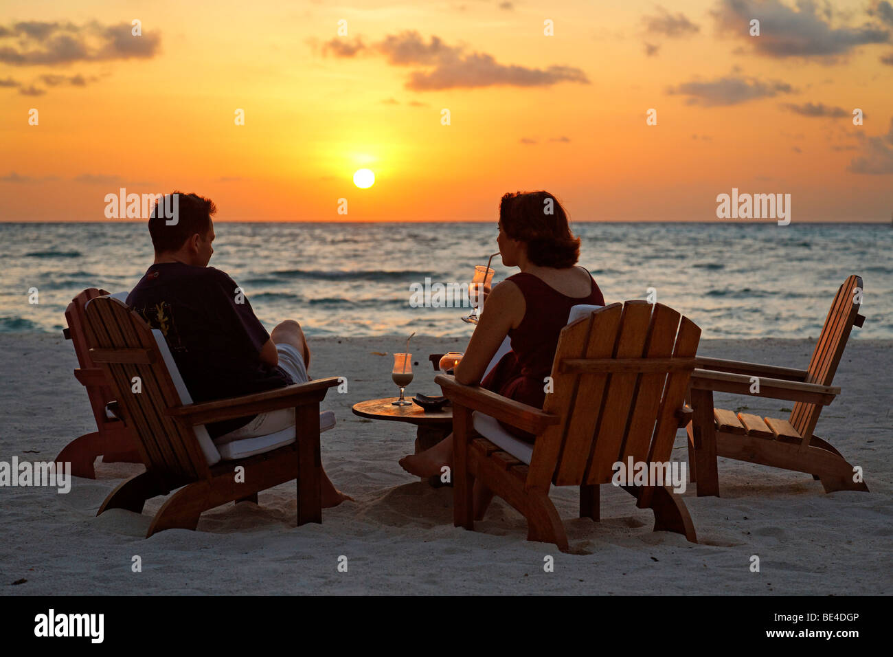 Couple sitting on chairs at the beach with long drinks in front of a golden sundown, Rihiveli, Island, Maldives, - Stock Image