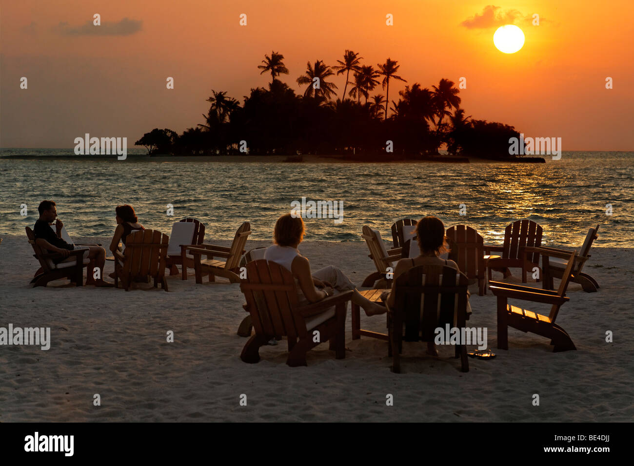 People are sitting on chairs at the beach with long drinks in front of a golden sundown, Maldive island, Rihiveli, - Stock Image
