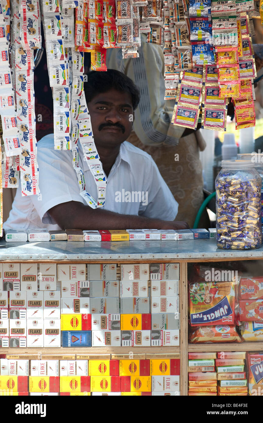 Indian shop keeper selling sweets and cigarettes in a small open fronted shop. Andhra Pradesh, India - Stock Image