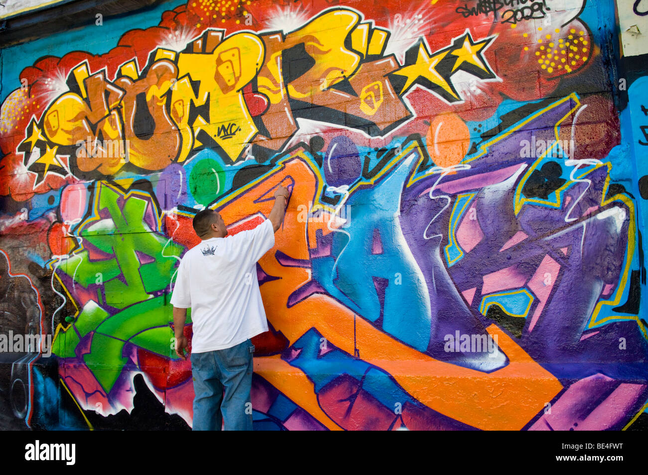 Graffiti artist works on his mural on the Five Pointz building in Long Island City in Queens - Stock Image
