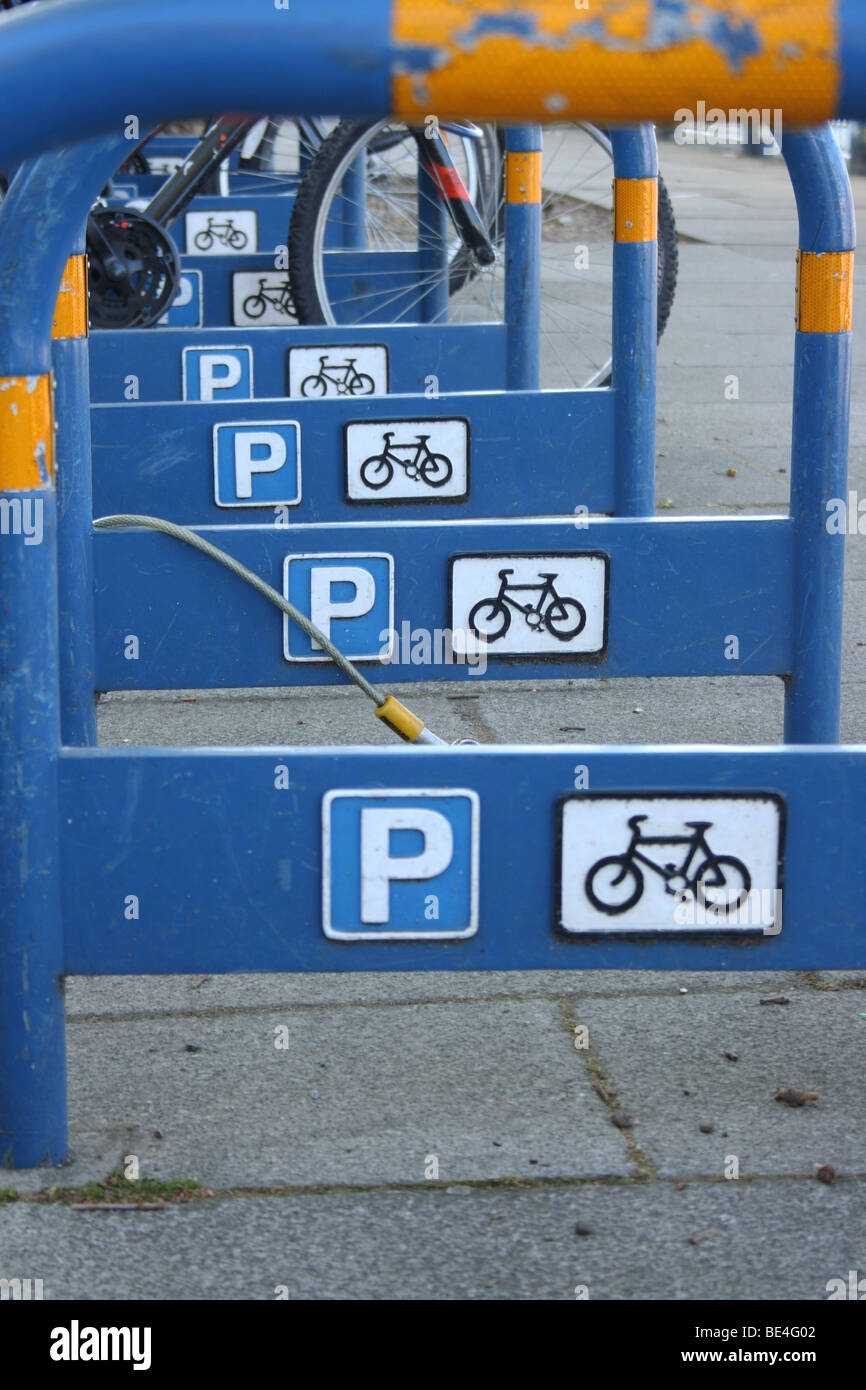 Row of strong and secure blue metal bicycle stands in street with Parking and Cycle symbols on sides at Putney, - Stock Image