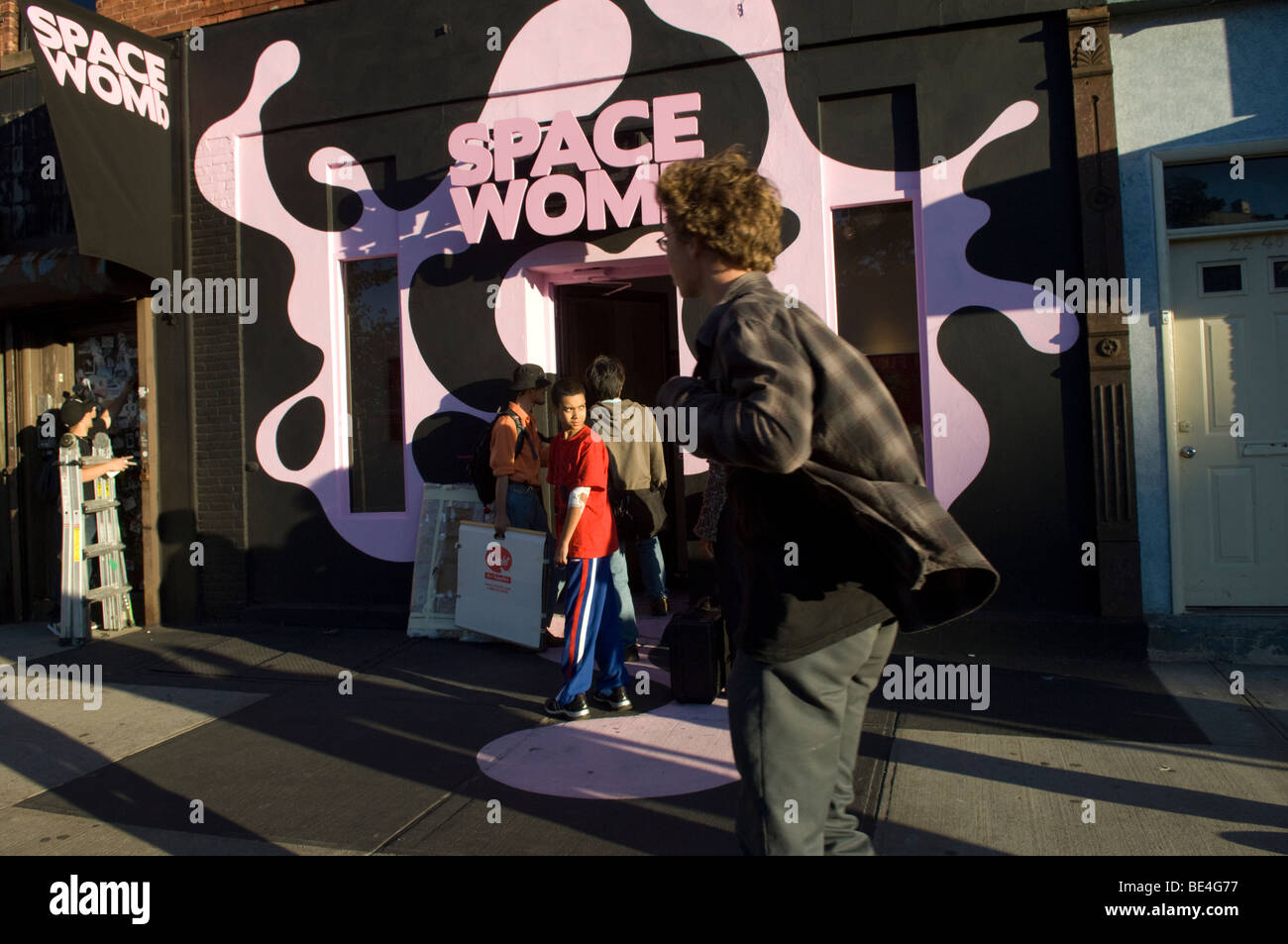 Artists carrying canvases enter the Space Womb gallery in preparation for Long Island City Open Gallery Night - Stock Image