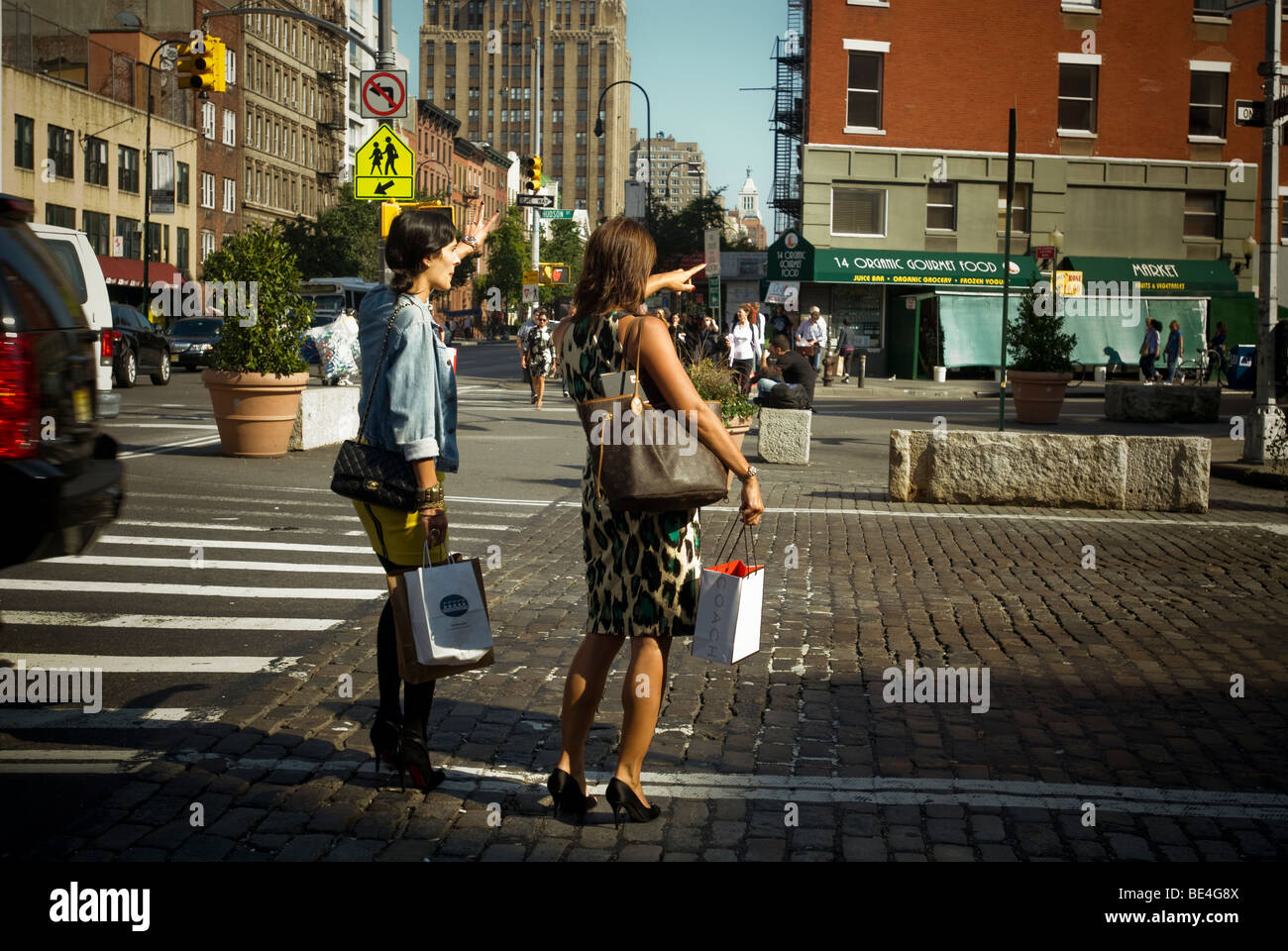 Shoppers attempt to hail a taxicab in the trendy Meatpacking District in New York - Stock Image