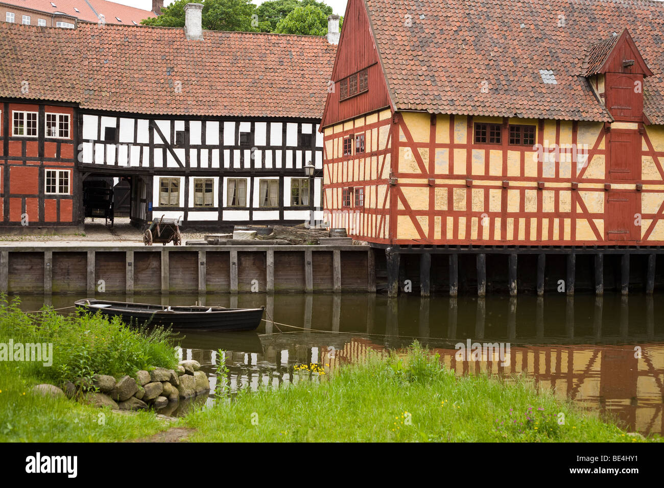 Half Timbered houses of old Aarhus. A small row boat floats quietly in the water in front of rows of traditional Stock Photo