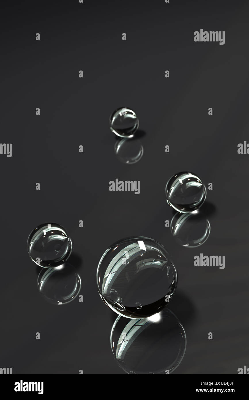 Glass marbles on glossy surface with reflections - Stock Image