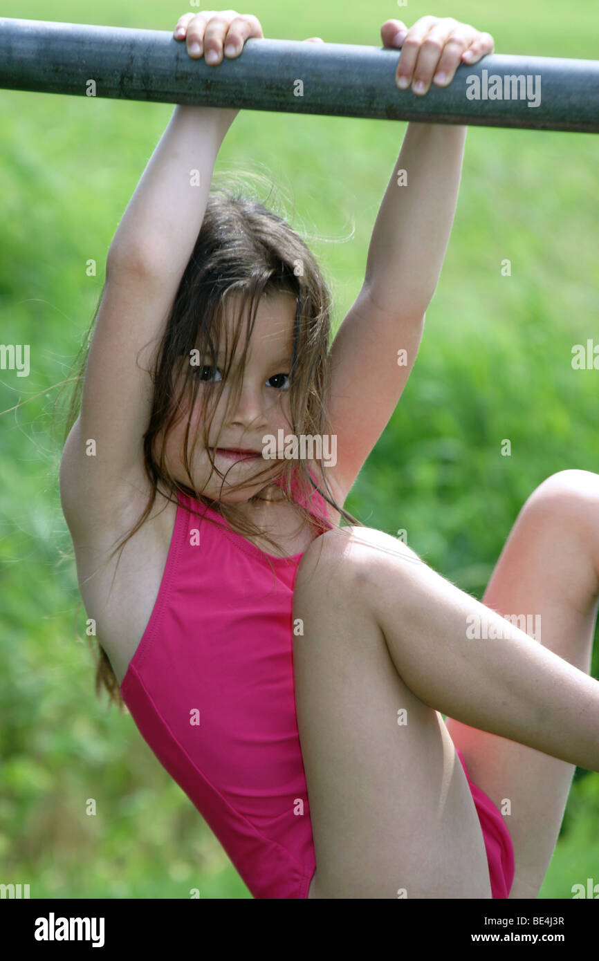 Cute 5 years old girl in bathing suit playing on climbing frame outside in summer - Stock Image