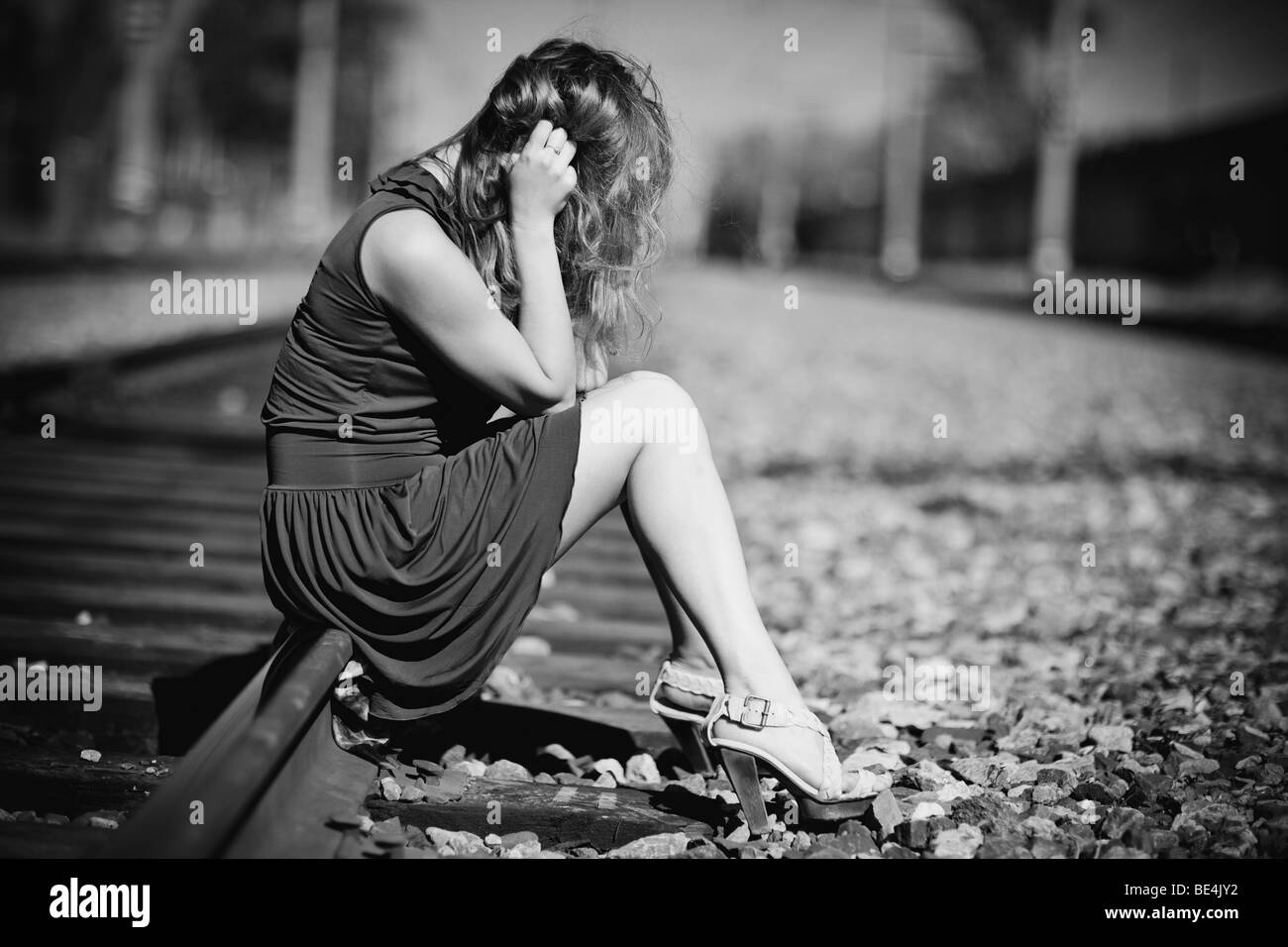 Young woman sitting on a rails sadness concept stock image