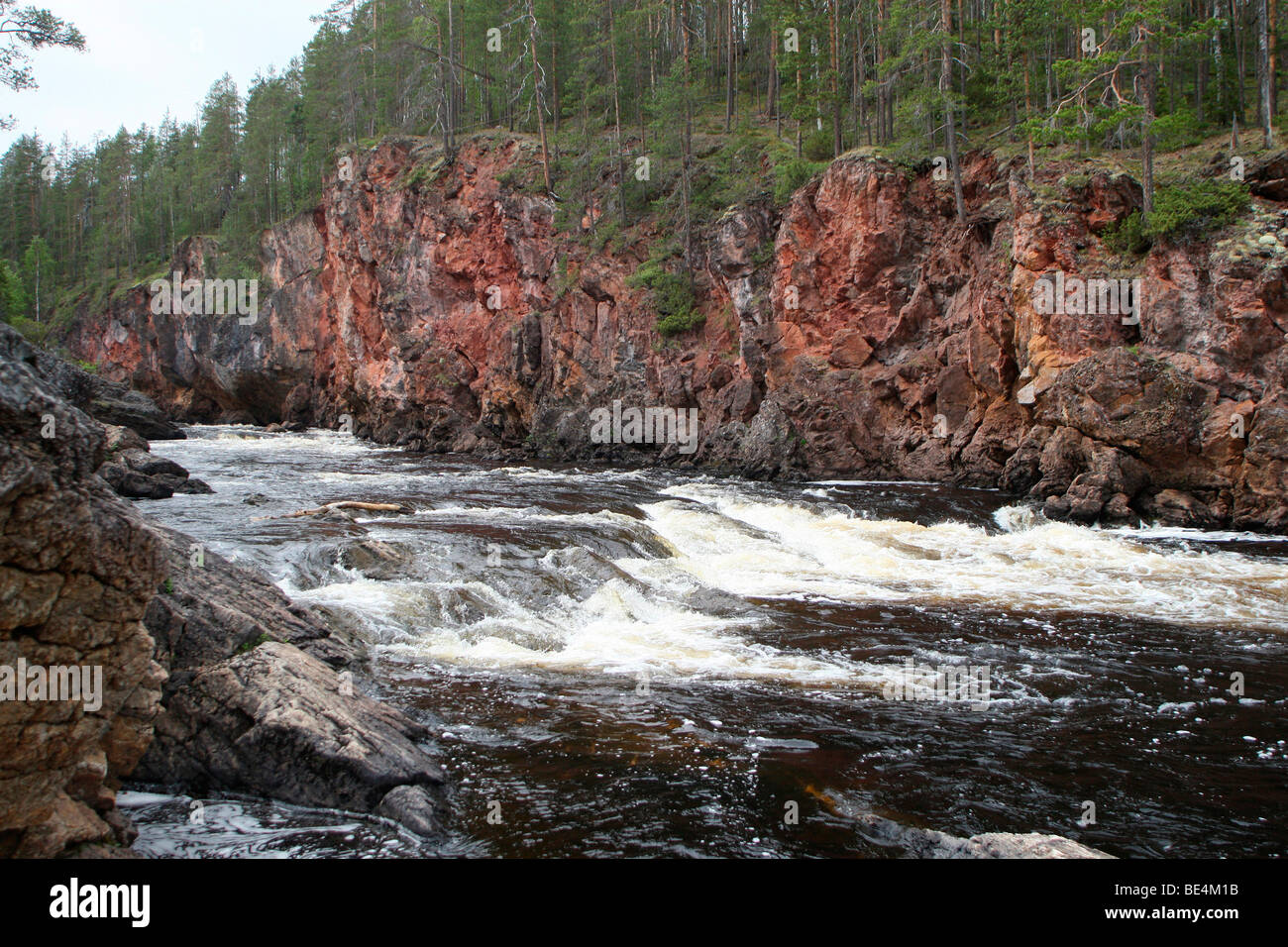 Red granite rocks in the rapids of the Oulankajoki river Oulanka in National Park, Lapland, Finland, Europe - Stock Image