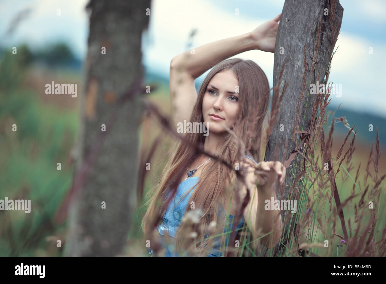 Young woman in a summer field calm portrait. Soft colors. - Stock Image