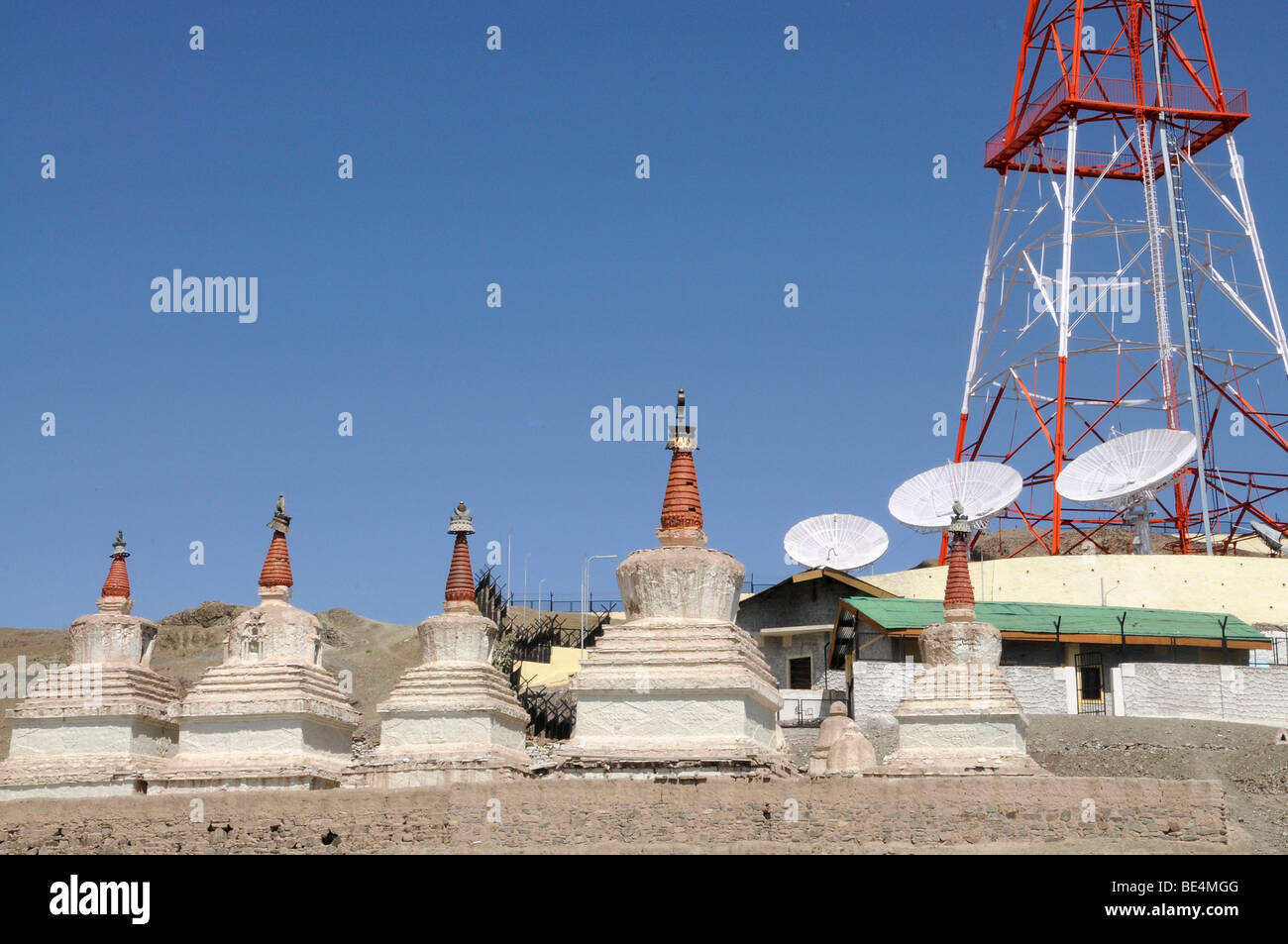 Buddhist chorten, sacred Tibetan architecture, in Stok, with satellite antennas of Ladakh's radio station, Northern - Stock Image