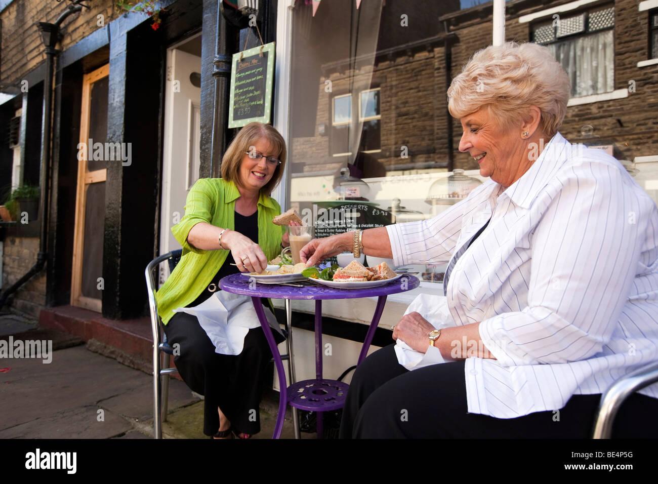 UK, England, Yorkshire, Haworth, Main Street, two women enjoying sandwich lunch outside in pavement cafe - Stock Image