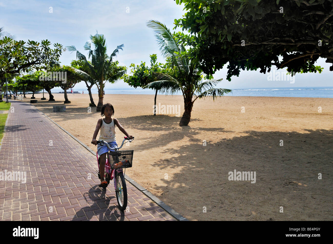 Beach with trees and bicyclist near Sanur, Denpasar, Bali, Indonesia, Southeast Asia - Stock Image
