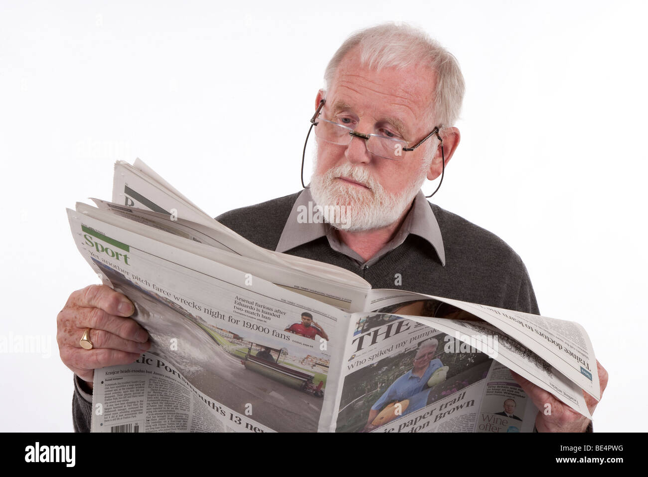 Older retired man reading daily newspaper. - Stock Image
