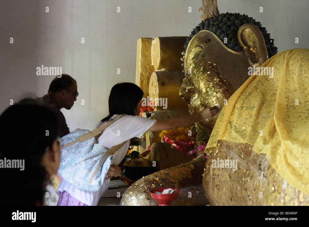 Buddhist sticking gold leaf on a recumbent statue of Buddha, Temple Wat Phra Sing, Chiang Mai, Northern Thailand, Stock Photo