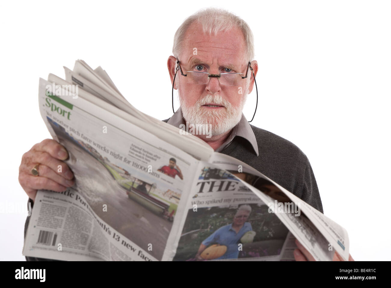 older man reading newspaper with angry expression stock photo