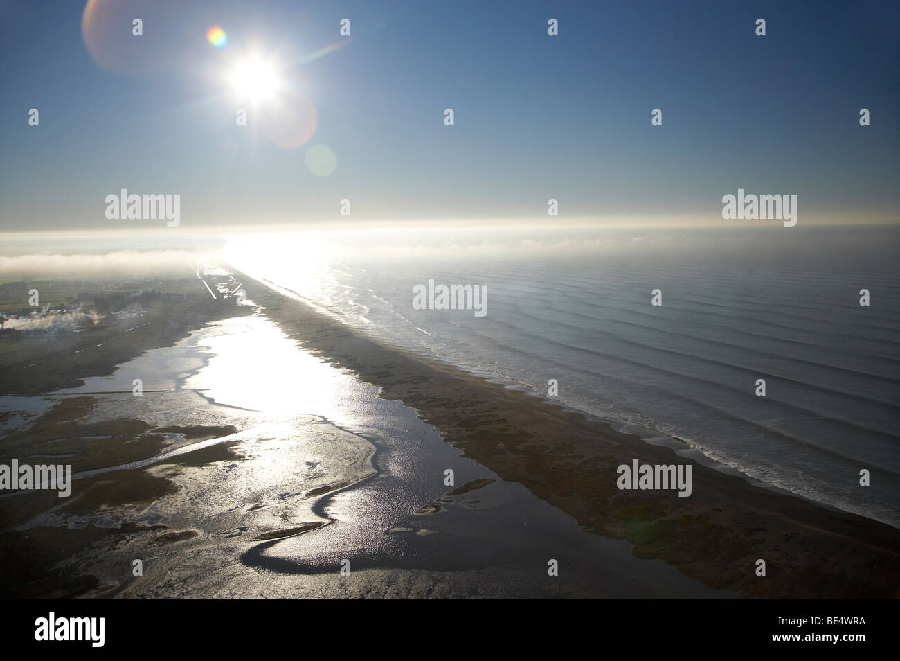 Sun over Washdyke Lagoon and Pacific Ocean, Timaru, South Canterbury, South Island, New Zealand - aerial - Stock Image