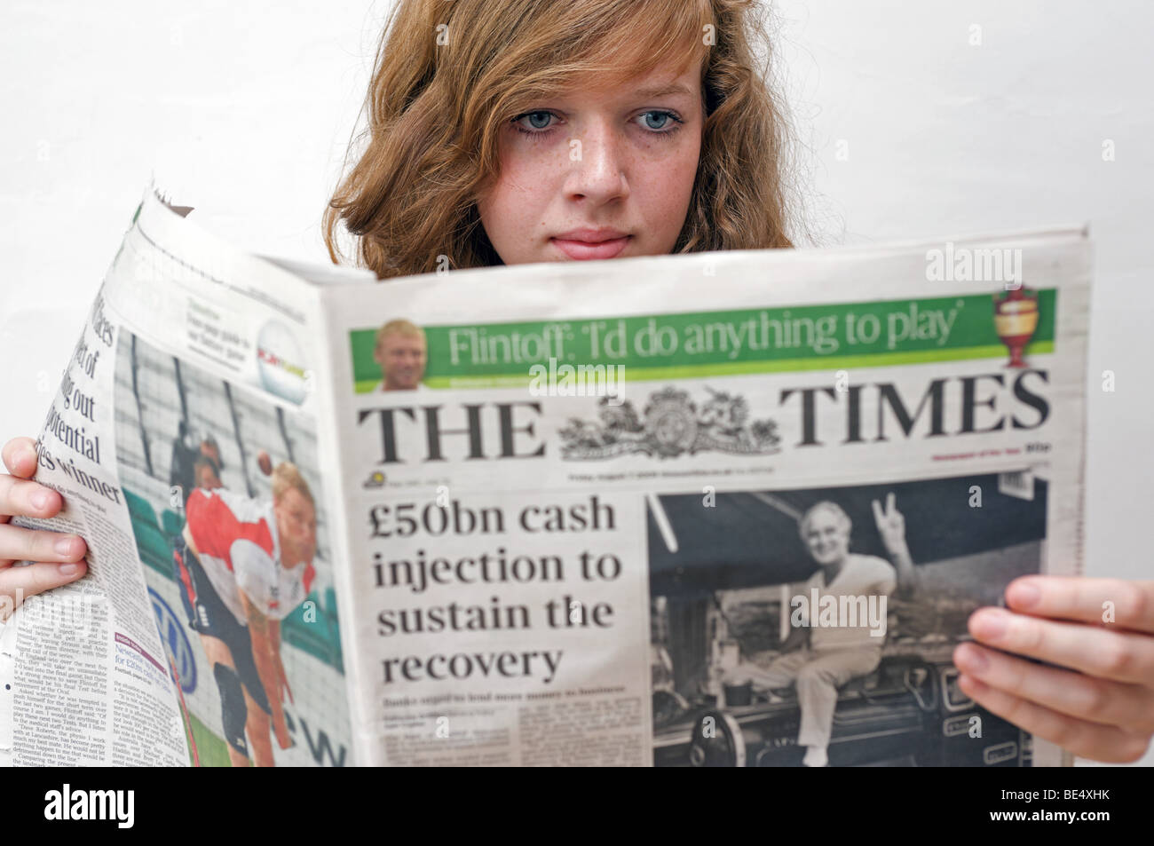 Teenager reading The Times newspaper. - Stock Image