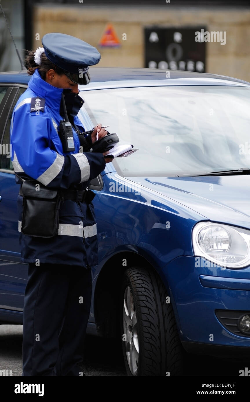 Traffic Warden Writing a Ticket for an Illegally Parked Vehicle, Oxford, England, United Kingdom. - Stock Image