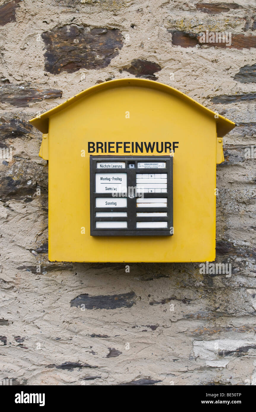 Old yellow metal letterbox on a quarrystone wall - Stock Image