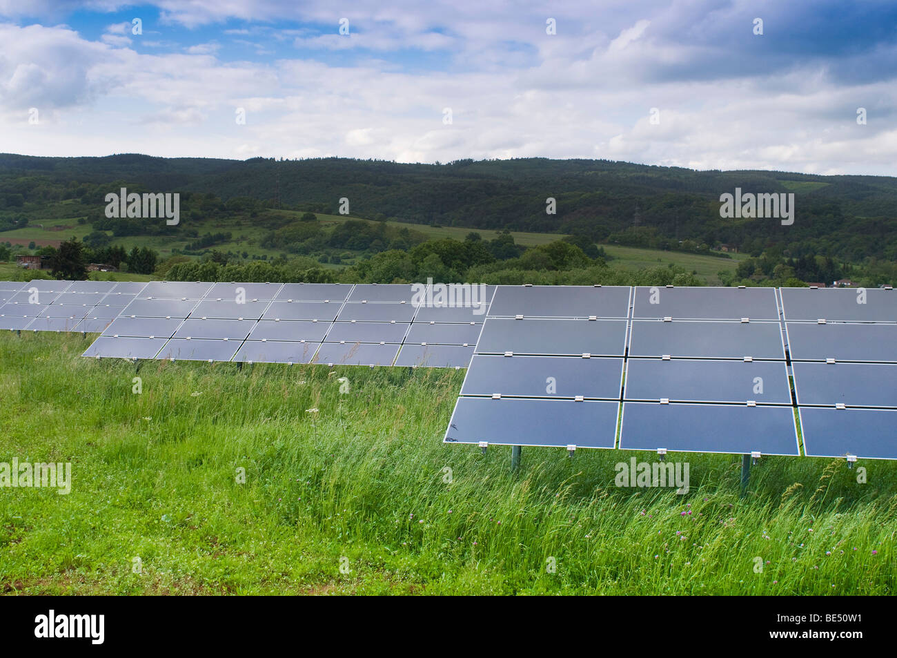 Photovoltaic, modules directed on different stands or racks on green meadow - Stock Image