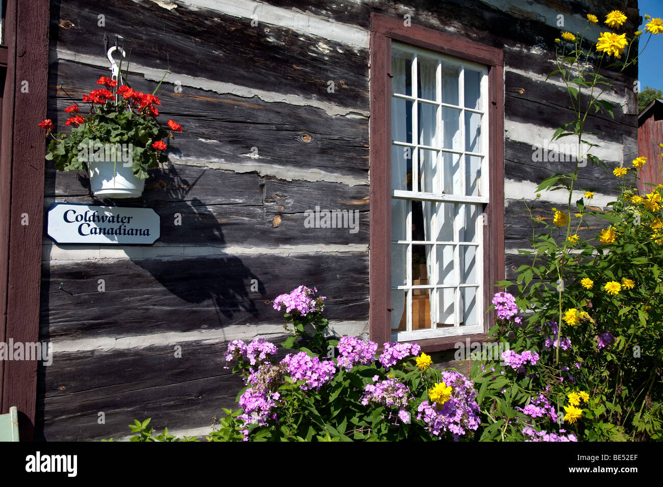 b9fcbc530579 Tradition Canadian Log Home for the 19th Century  window flowers exterior