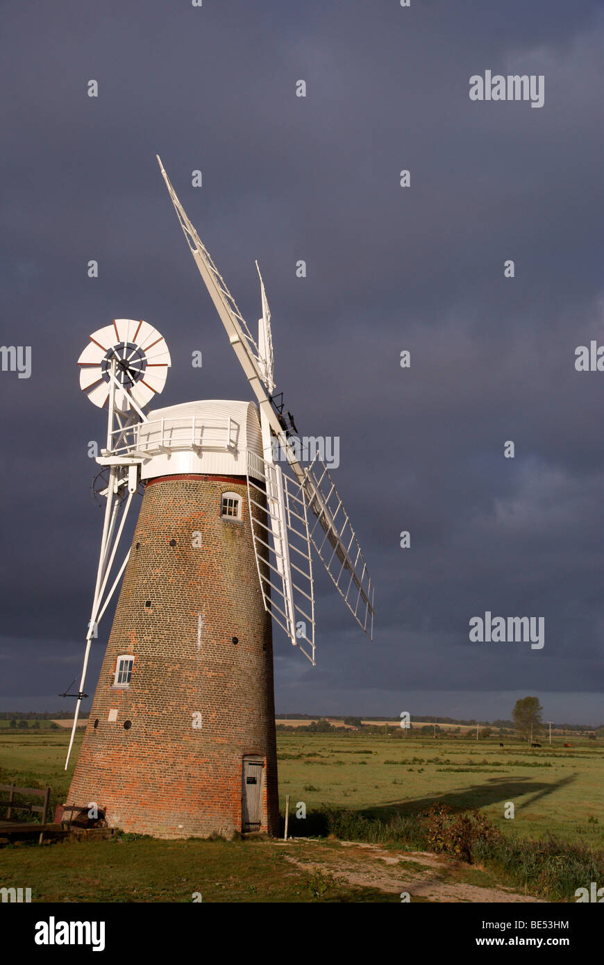Morning sunlight catches Hardley drainage mill against a stormy dark sky - Stock Image