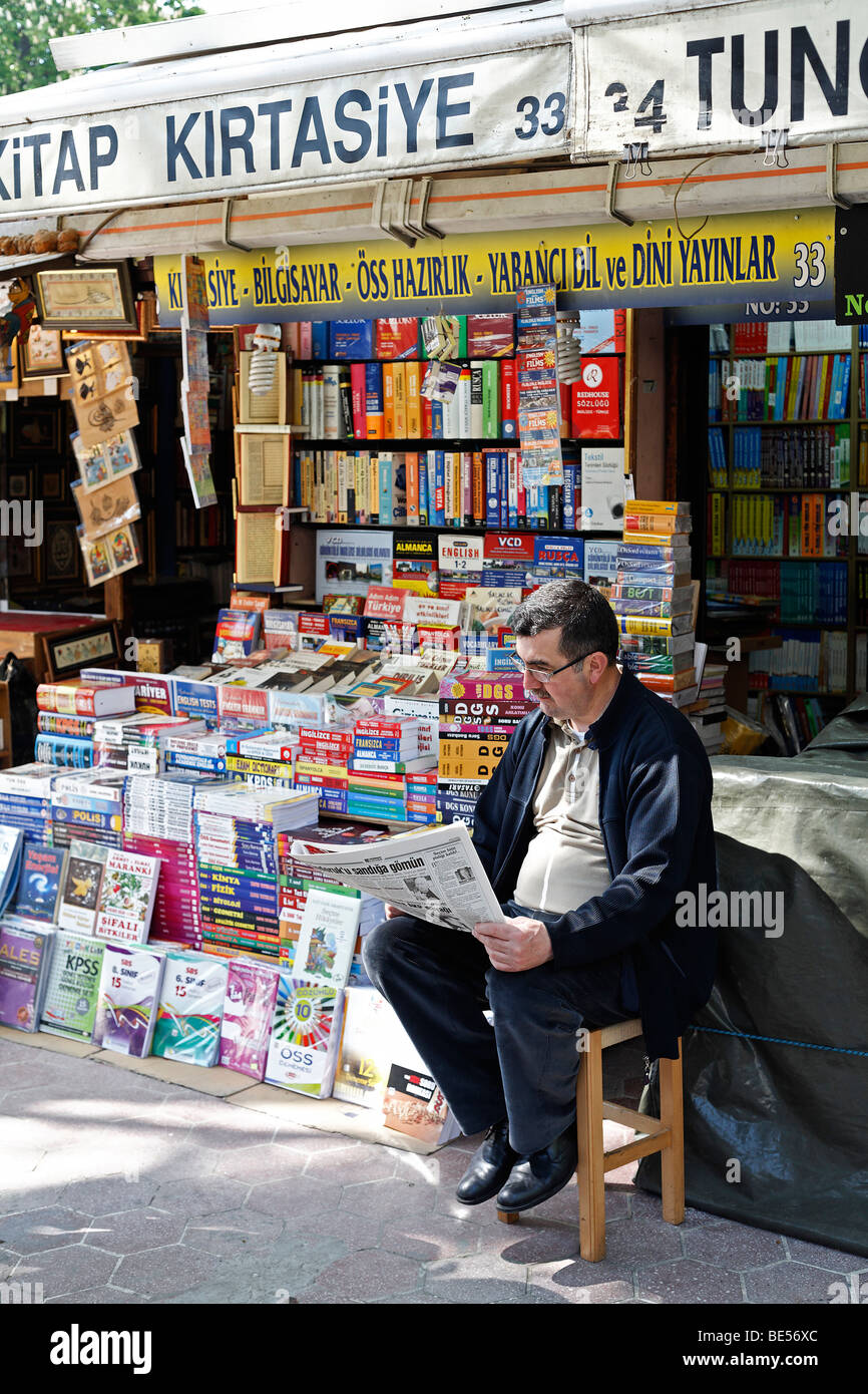 Bookseller sits in front of his stall, reading newspapers, book bazaar, Beyazit Square, Istanbul, Turkey - Stock Image