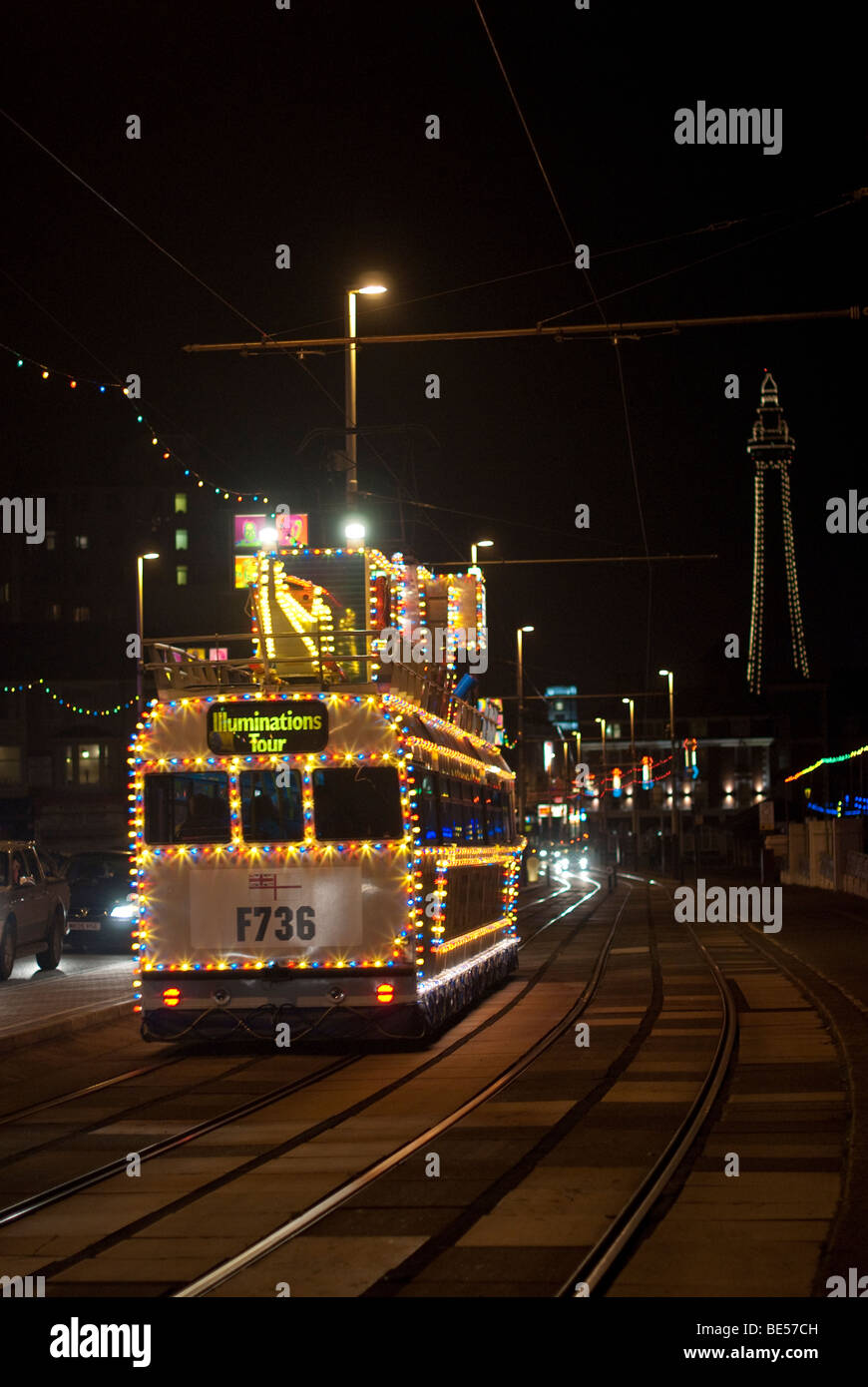Blackpool, UK: Decorated with light, a Tram running along the promenade towards the Tower during Blackpool Illuminations Stock Photo