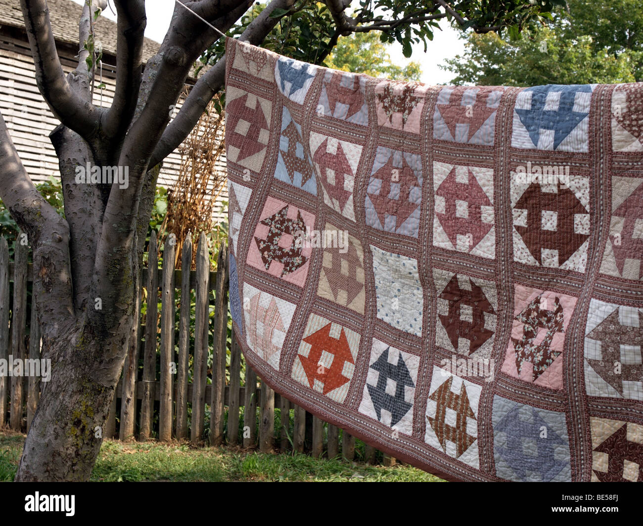 Handmade quilt hanging outside to dry on the clothesline. The clothesline is strung between 2 trees. In the background - Stock Image