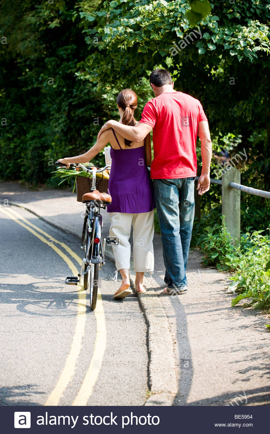 A man and woman walking together with a bicycle and shopping - Stock Image