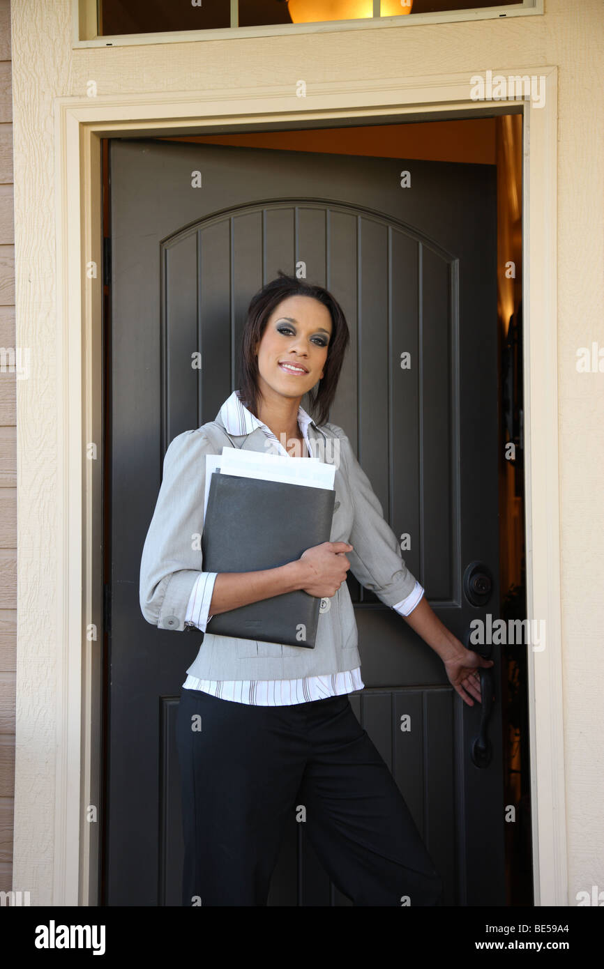 Young female Realtor opening front door of home Stock Photo