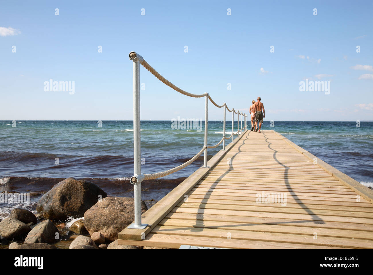 A man and a woman walking on a bathing jetty for a cooling swim in the afternoon on a warm and sunny summer day - Stock Image