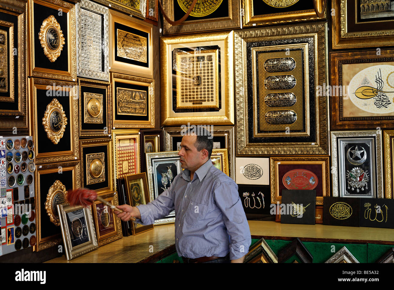 Man brushing the dust off golden frame, with calligraphic emblems, book bazaar, Beyazit Square, Istanbul, Turkey Stock Photo