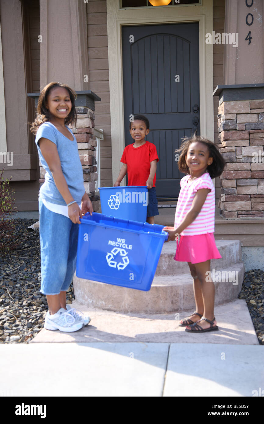 Three children with recycle bin - Stock Image