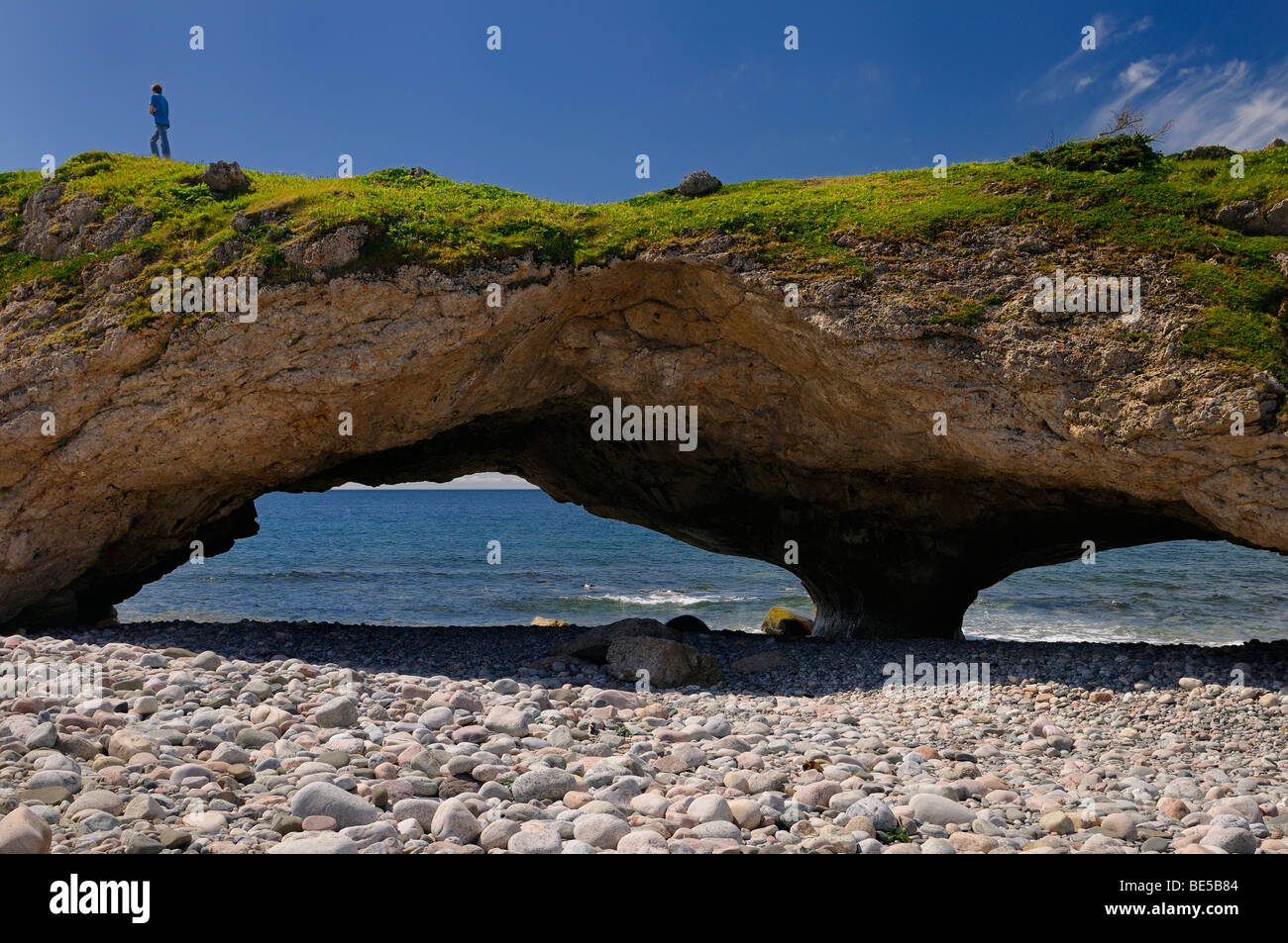 Boy walking on the roof of an arch at Arches Provincial Park Newfoundland Canada on the Gulf of the St. Lawrence - Stock Image