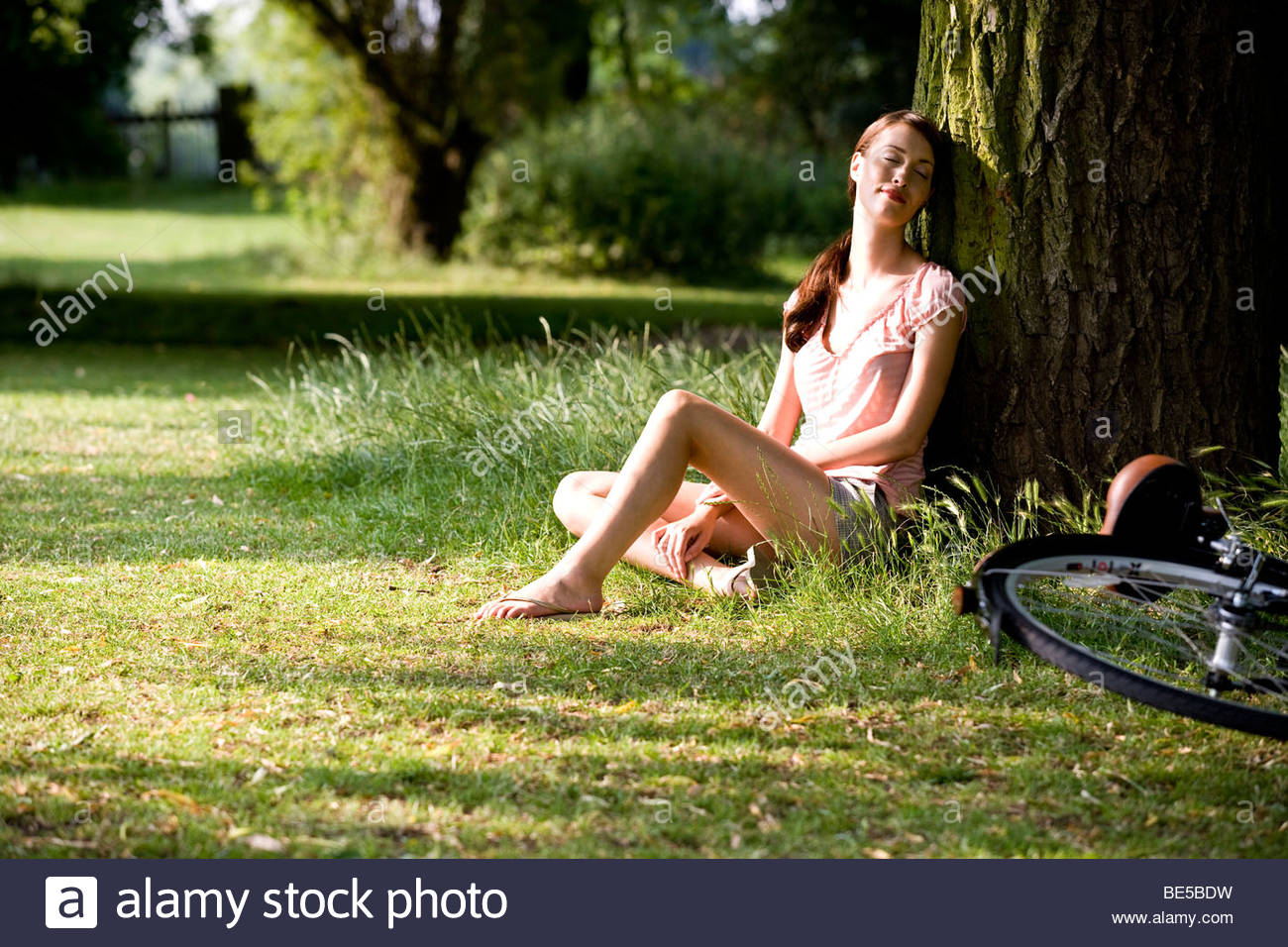 A young woman resting up against a tree trunk - Stock Image