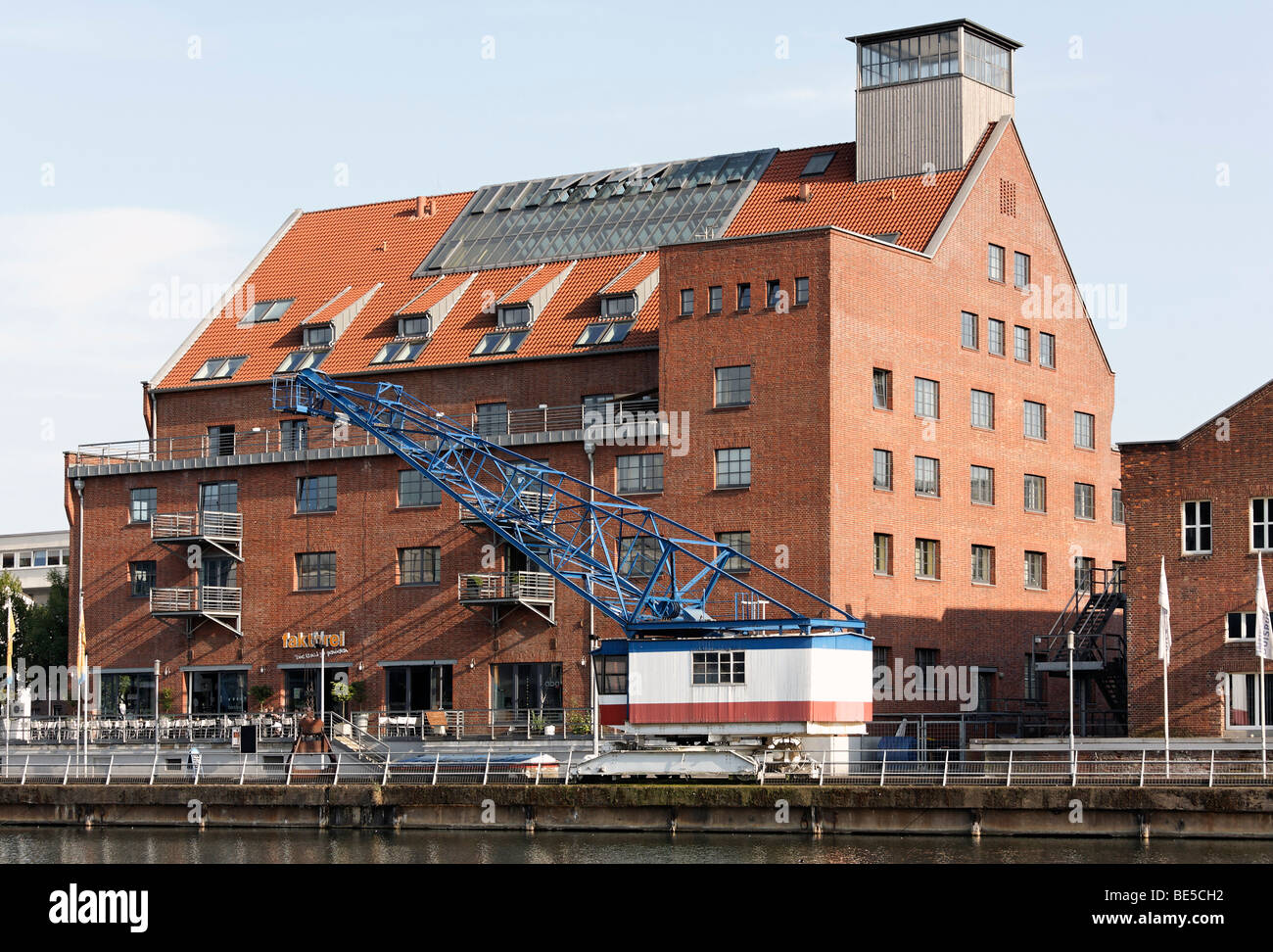 Renovated storage building, Faktorei 21, historical harbor crane, inner harbor, Duisburg, Ruhrgebiet area, North Stock Photo