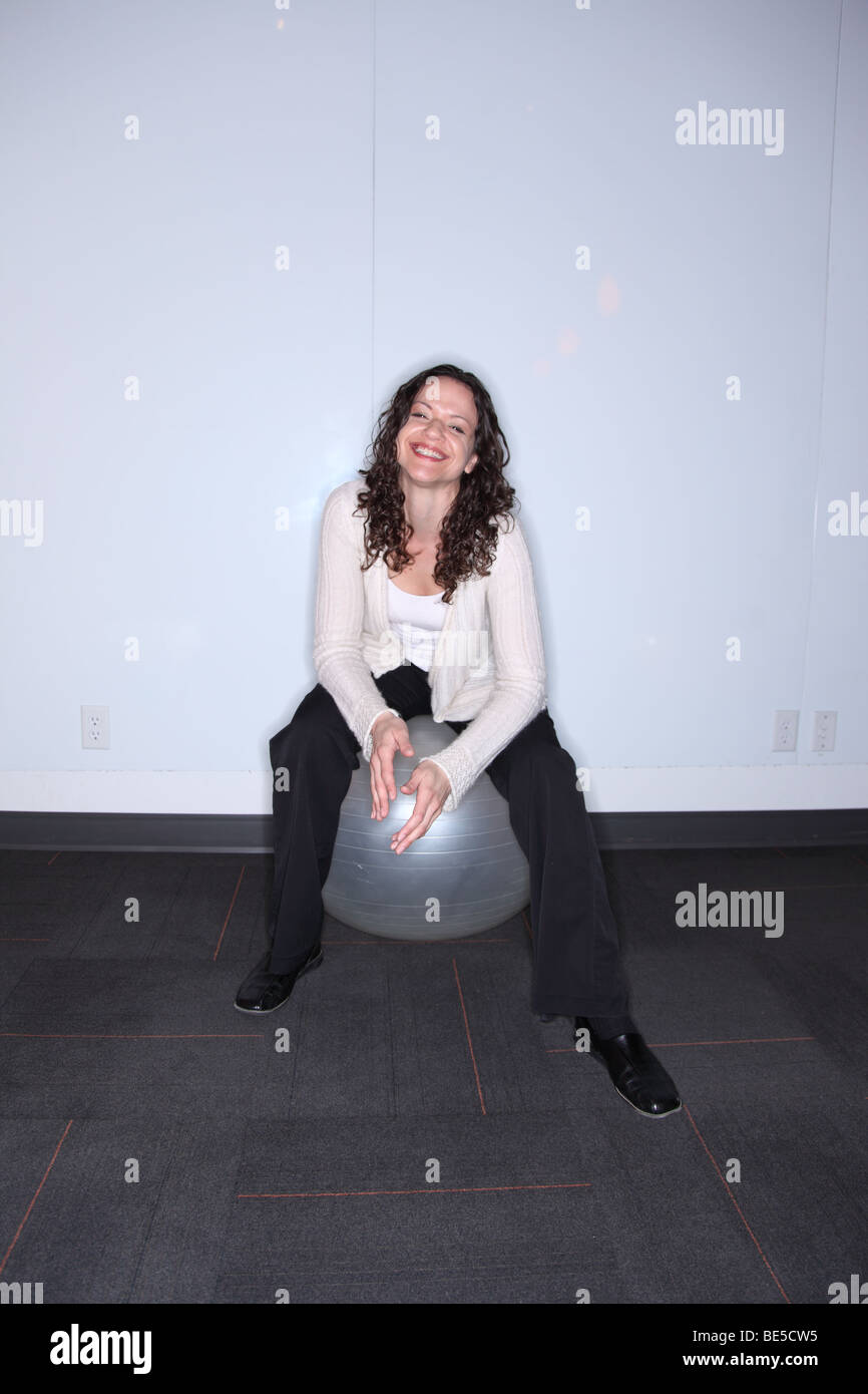 Woman sitting on ball smiling at camera - Stock Image