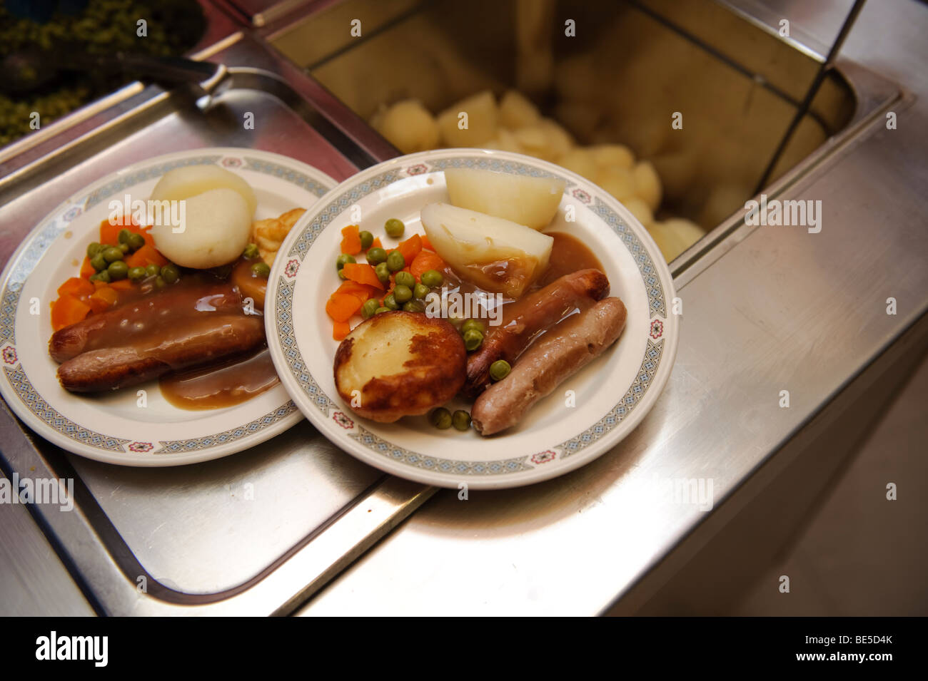School dinners - sausage vegetables and potatoes -  served up on plates in a primary school canteen hall, Wales Stock Photo