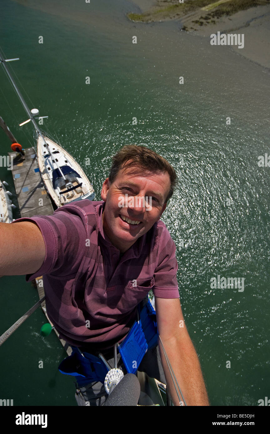 Neil Foster at the top of a Southerly 35 mast. Stock Photo
