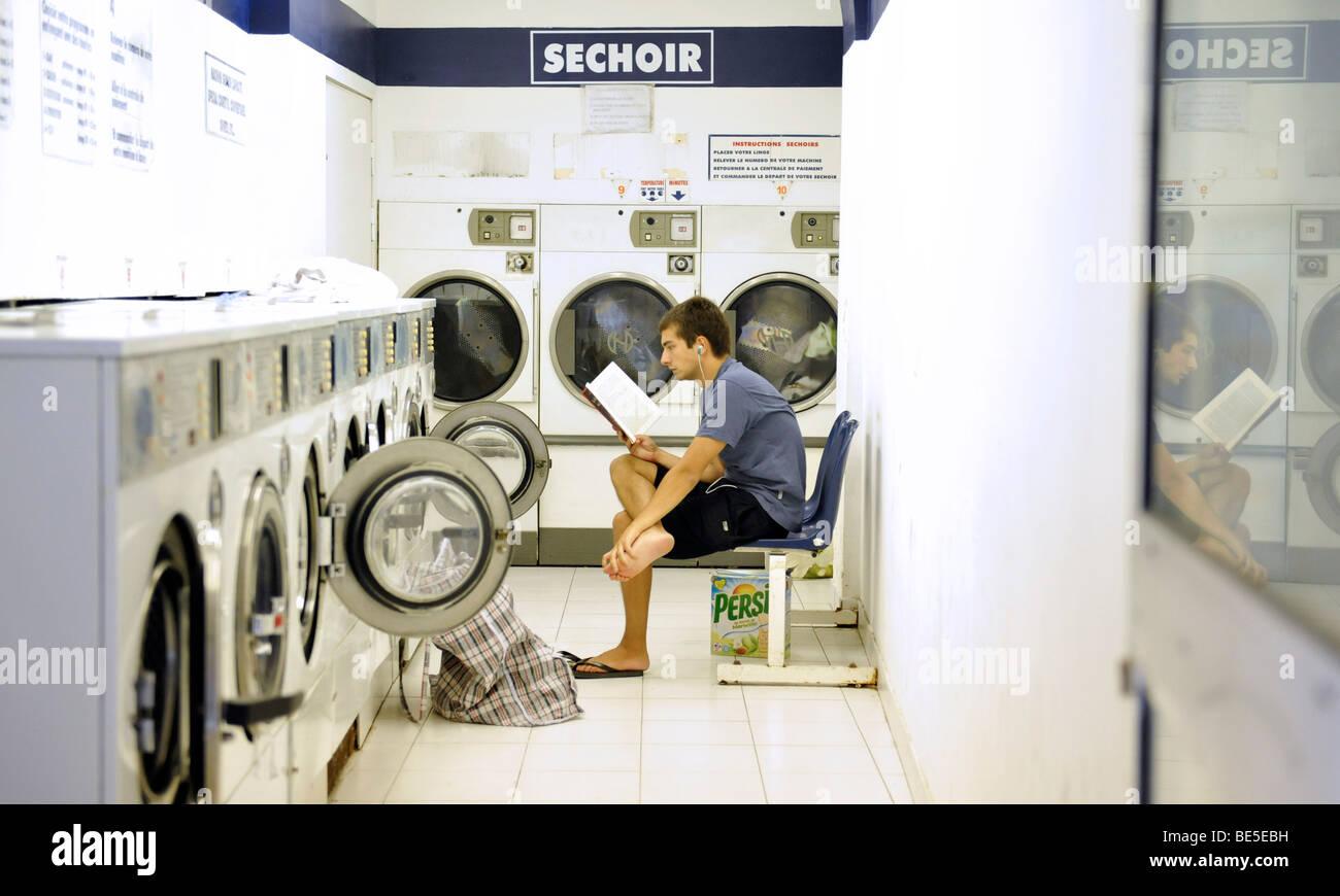 man laundrette washing reading persil - Stock Image