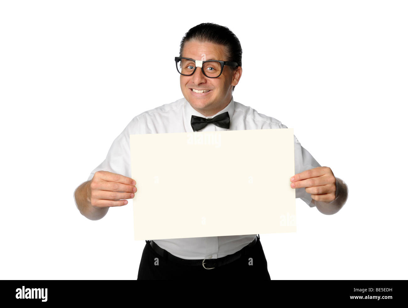 Nerd smiling and holding blank sign isolated over white - Stock Image