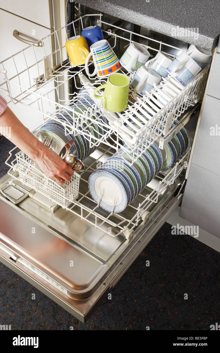 Dishwasher, taking out the dishes Stock Photo