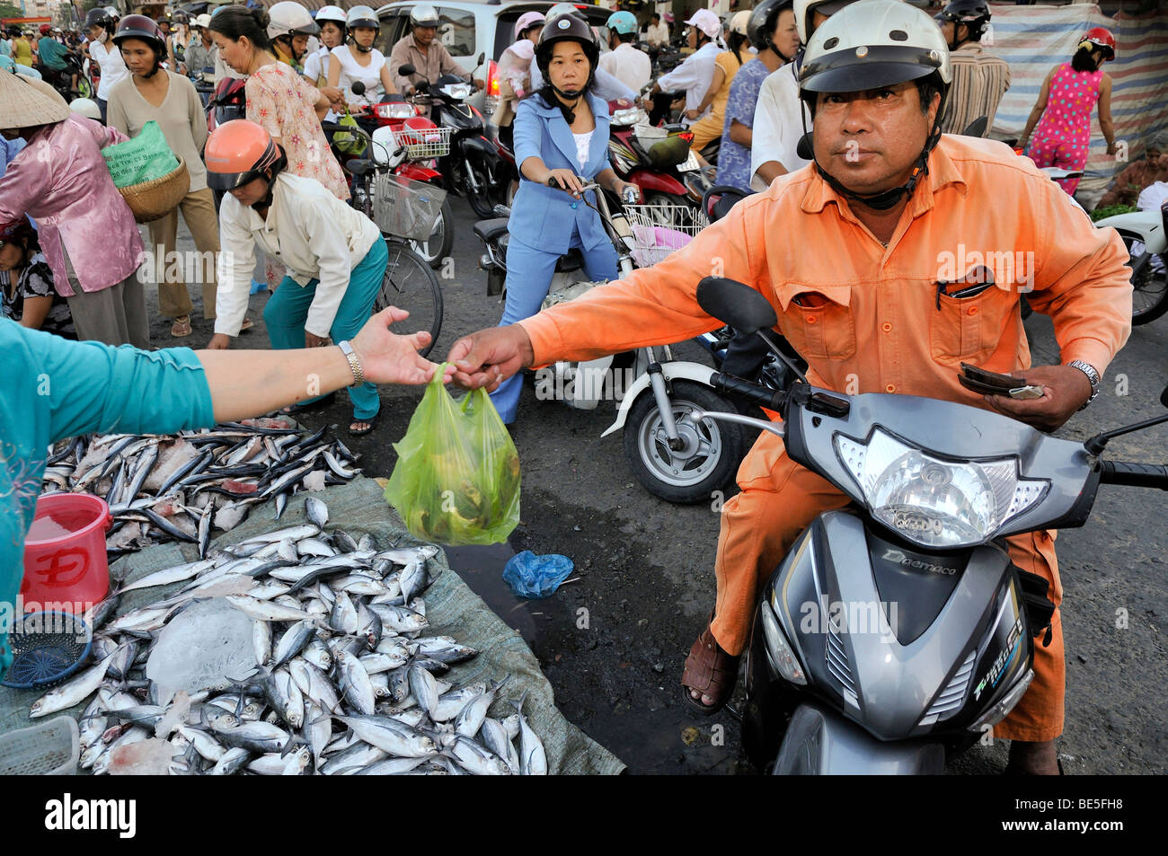 Man on scooter buys at the fish market, Vinh Longh, Mekong Delta, Vietnam, Asia - Stock Image